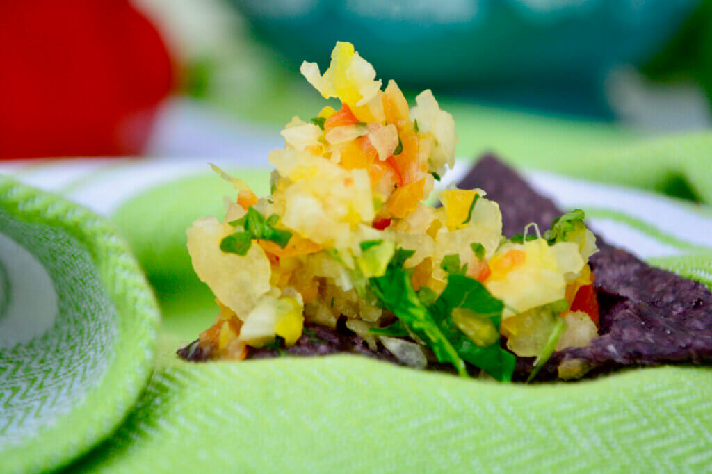 A blue corn tortilla chip sits front and center topped with a heap of multi-colored pico de gallo. A blue patterned bowl and red pepper are blurred in the background with a green and white stripped cloth underlaying all the deliciousness!