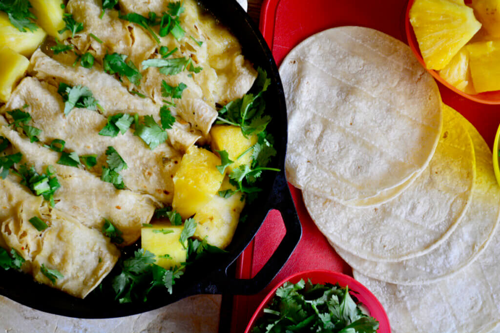 A warm skillet of pineapple enchiladas is featured in the top left corner surrounded by cilantro and tortillas.