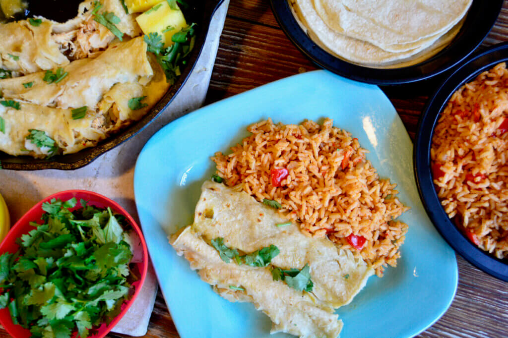 A turquoise plate of two pineapple enchiladas and a side of Spanish rice is featured in the bottom left. Tortilla's, cilantro, and a skillet full of enchiladas surrounds the brightly colored plate.