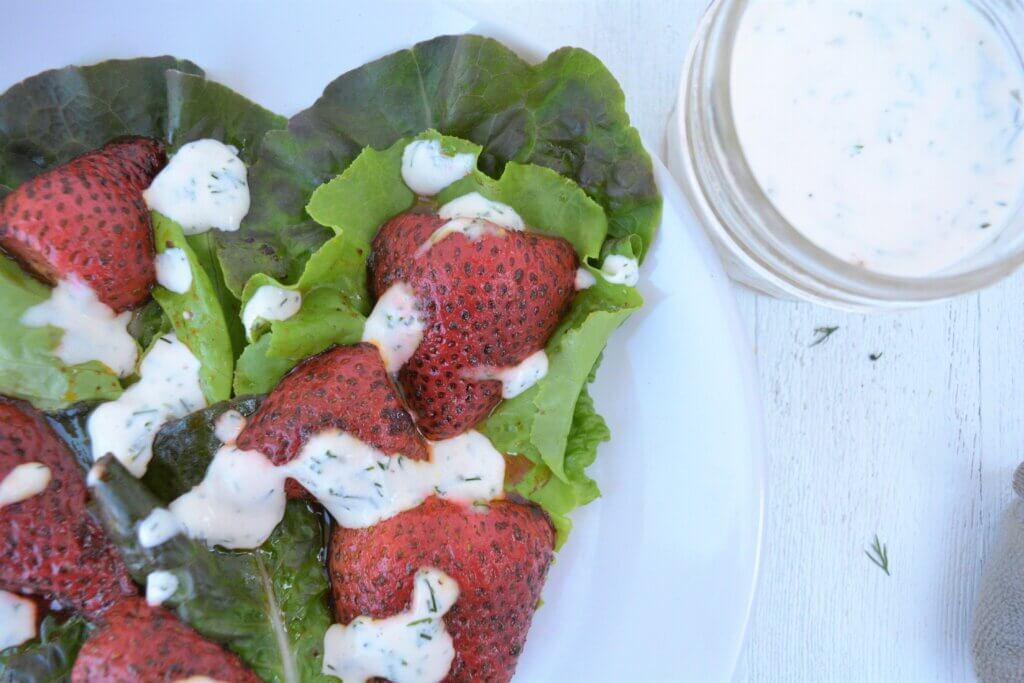 low potassium strawberrie and greens salad on plate with low phosphorus creamy dressing for kidney diet