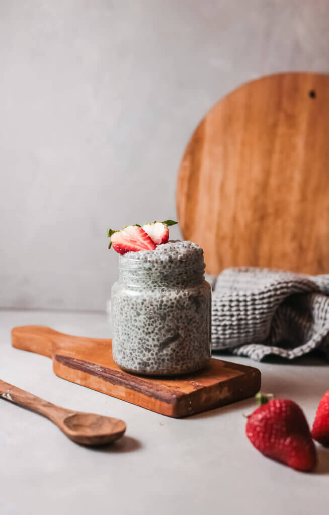 Chia pudding with spoon on wooden board