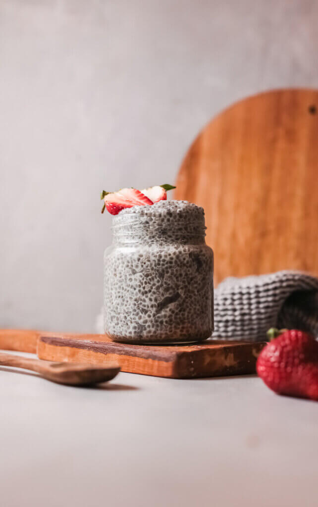Close up view chia pudding with spoon on wooden board