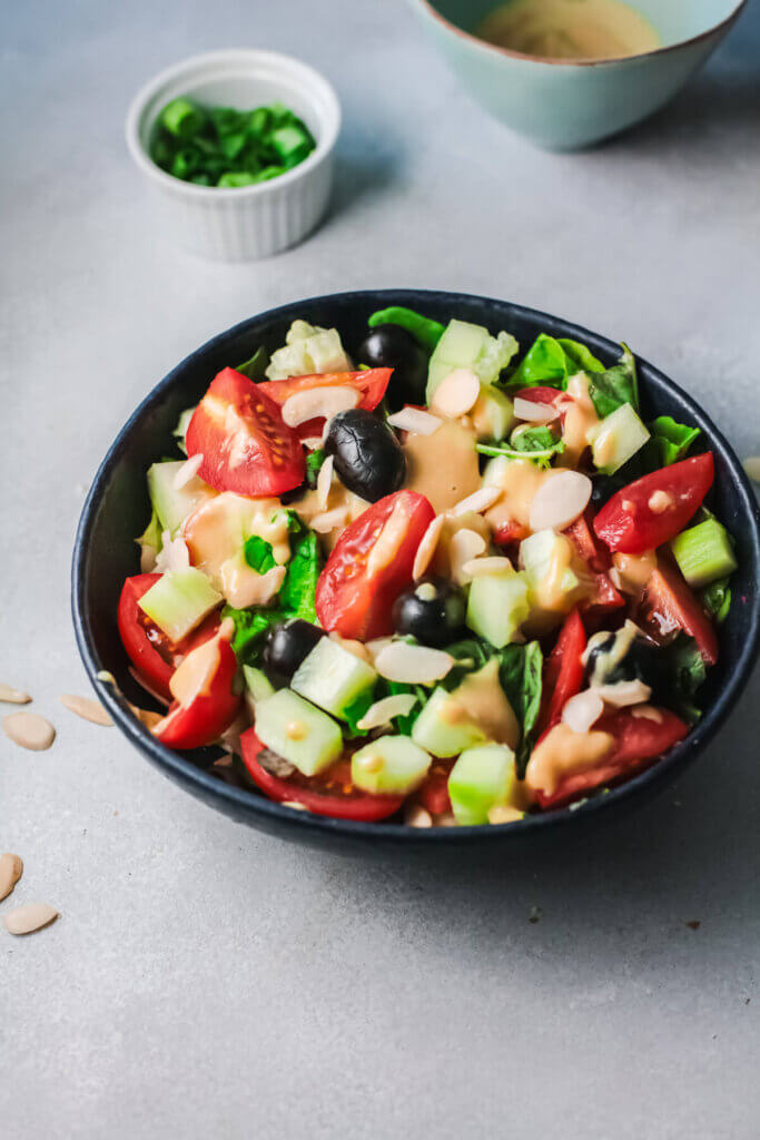 Top angle view of tomato olive, tahini salad with bowl of green onions in a white bowl