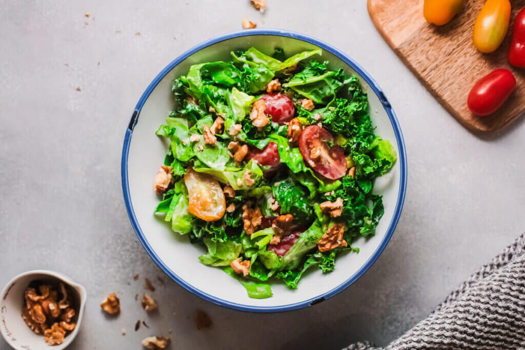 Top view creamy caesar salad keto in a bowl with cherry tomato on wooden board and small bowl of walnuts