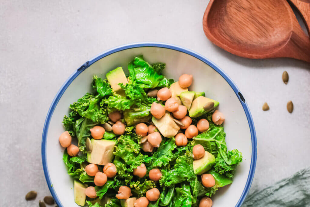 Overhead view of lemony kale salad with chickpeas in a white bowl with wooden spoon and green tea towel