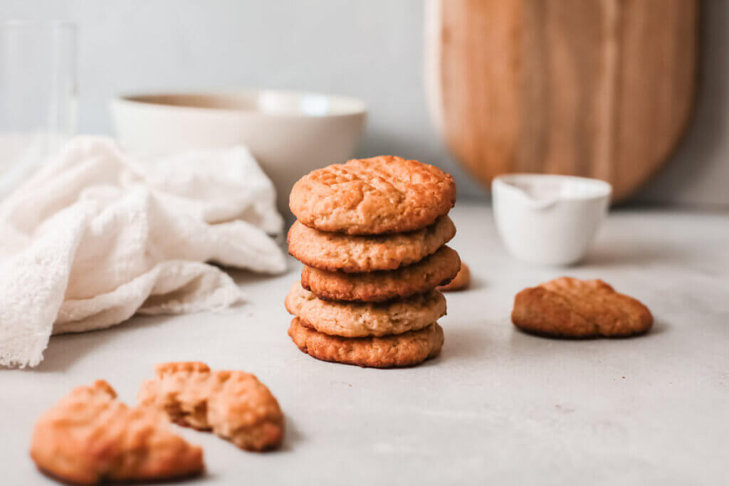 Stack of peanut butter maple cookies with white tea towel, white bowl and wooden board in the background