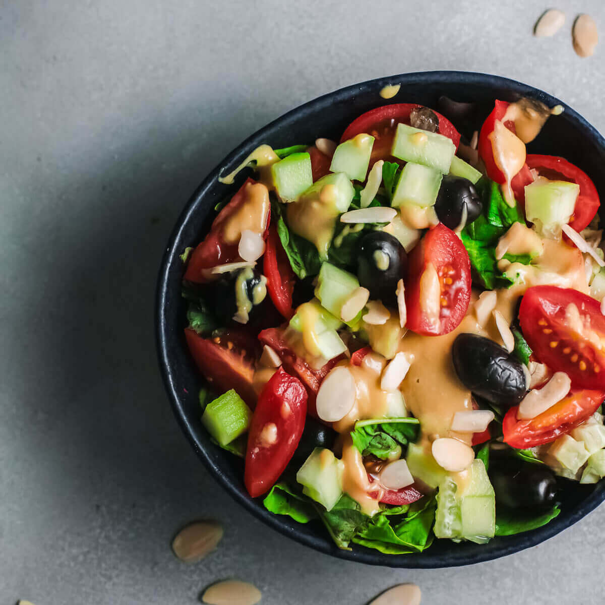 Top view olive, tahini and tomato salad with small dish of almonds