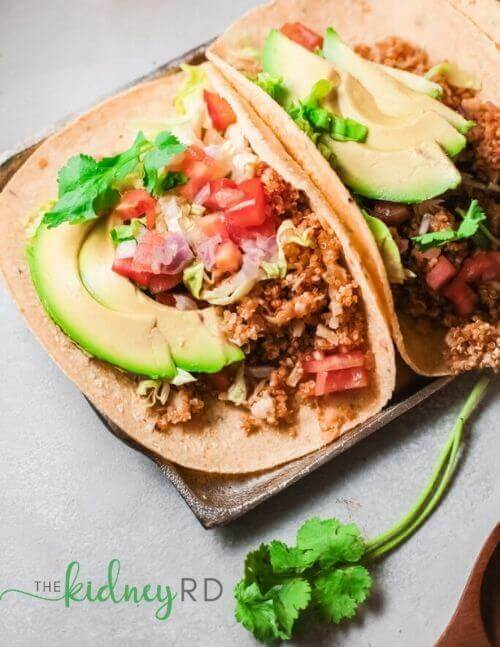 Close up view of plant-based quinoa and cauliflower tacos on a silver serving tray topped with avocado, pico de gallo and cilantro