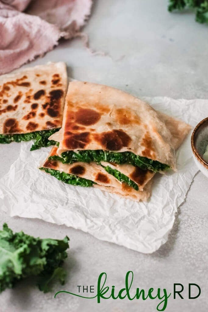 Top view of creamy kale vegan quesadilla quarters on parchment with kale and small bowl of coconut yogurt and pink tea towel in background
